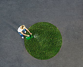 Woman watering circle of grass on pavement