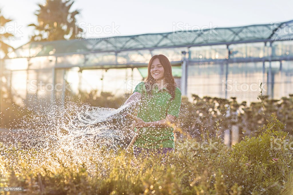 Woman watering plants at garden center stock photo