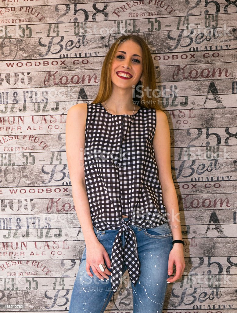 Woman wearing a black and white checked shirt and jeans stock photo