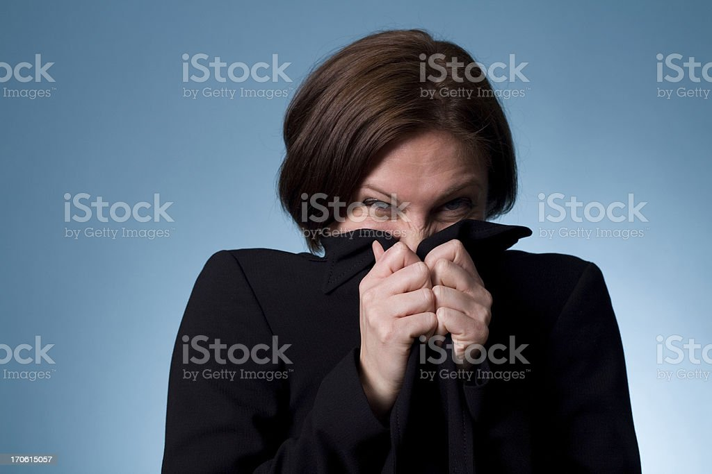A woman wearing a dark dress trying to hide her face stock photo