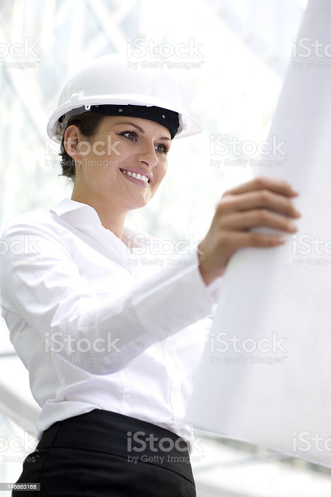 Woman wearing a hardhat holding plans royalty-free stock photo