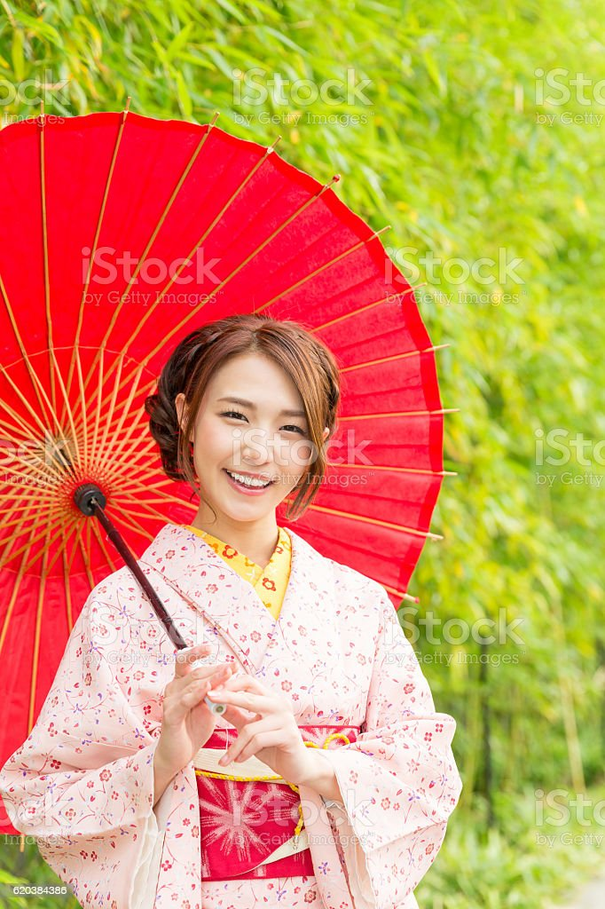 Woman wearing a kimono with a red umbrella stock photo