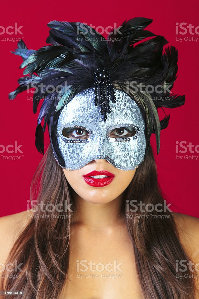 Woman wearing a masquerade mask red background stock photo