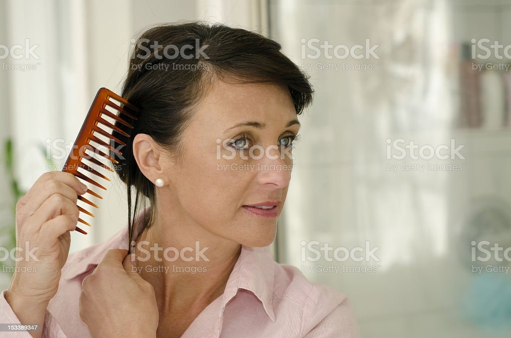 A woman wearing a pink shirt combing her hair stock photo