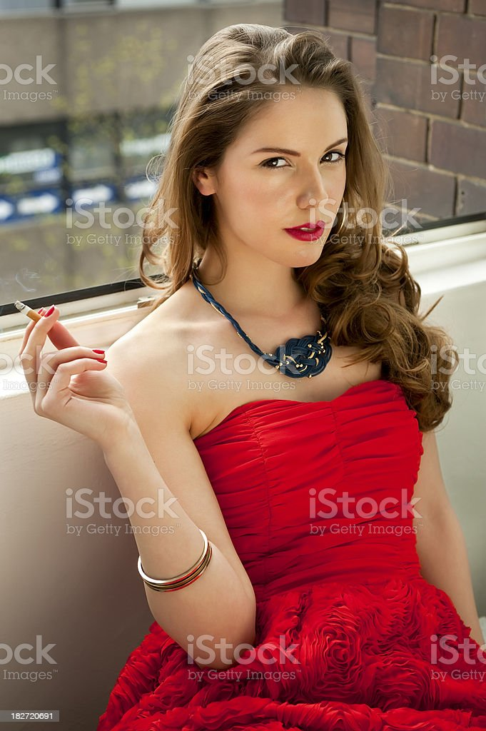 Woman wearing a red dress smoking in the window royalty-free stock photo