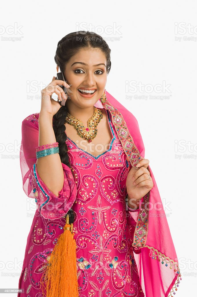 Woman wearing a salwar kameez and talking on mobile phone stock photo