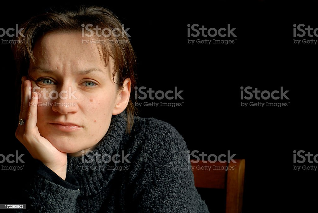 A woman wearing a sweater sitting in a chair depressed stock photo