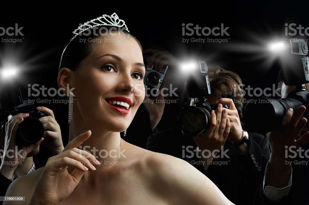 Woman wearing a tiara being photographed by paparazzi royalty-free stock photo