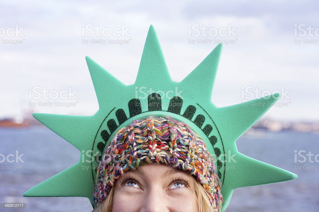 Woman wearing a tourist Statue of Liberty crown on island stock photo
