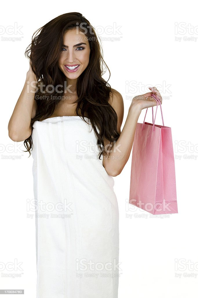 Woman wearing a towel and holding gift bag royalty-free stock photo
