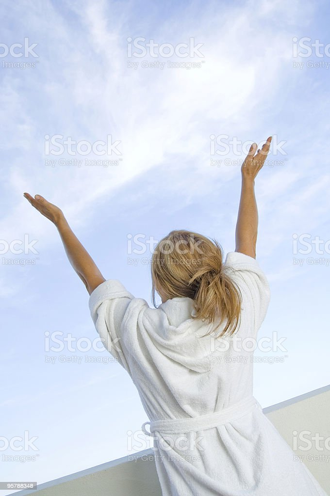 Woman wearing bathrobe, stretching her arms royalty-free stock photo