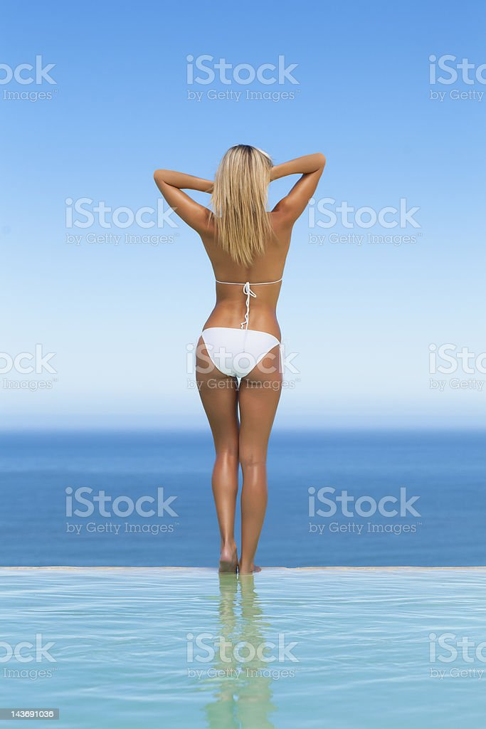 Woman wearing bikini by infinity pool stock photo