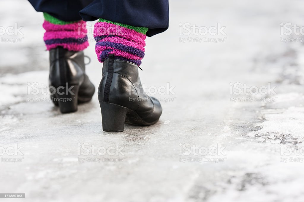Woman wearing black boots with heels walking on ice stock photo