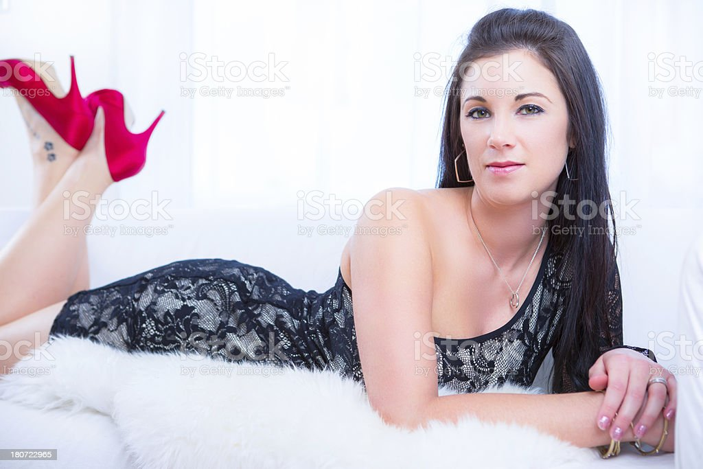 Woman wearing black dress on couch royalty-free stock photo