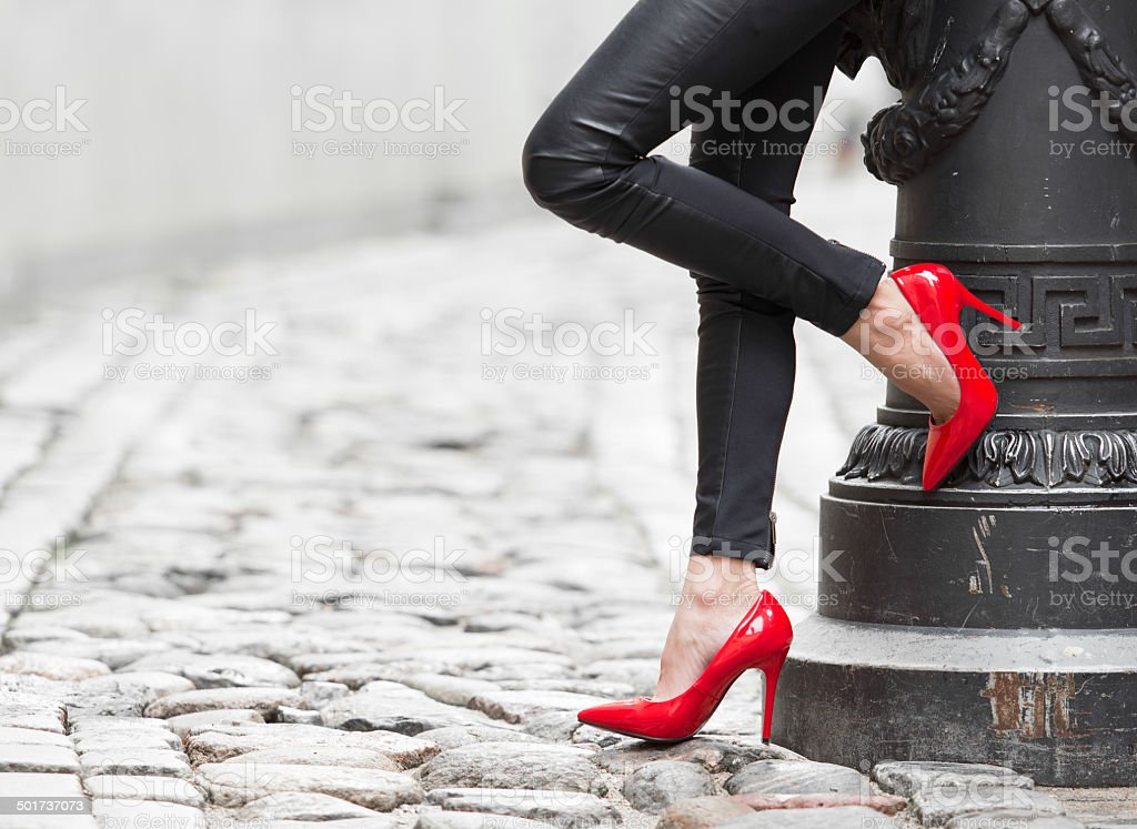 Woman wearing black leather pants and red high heel shoes stock photo