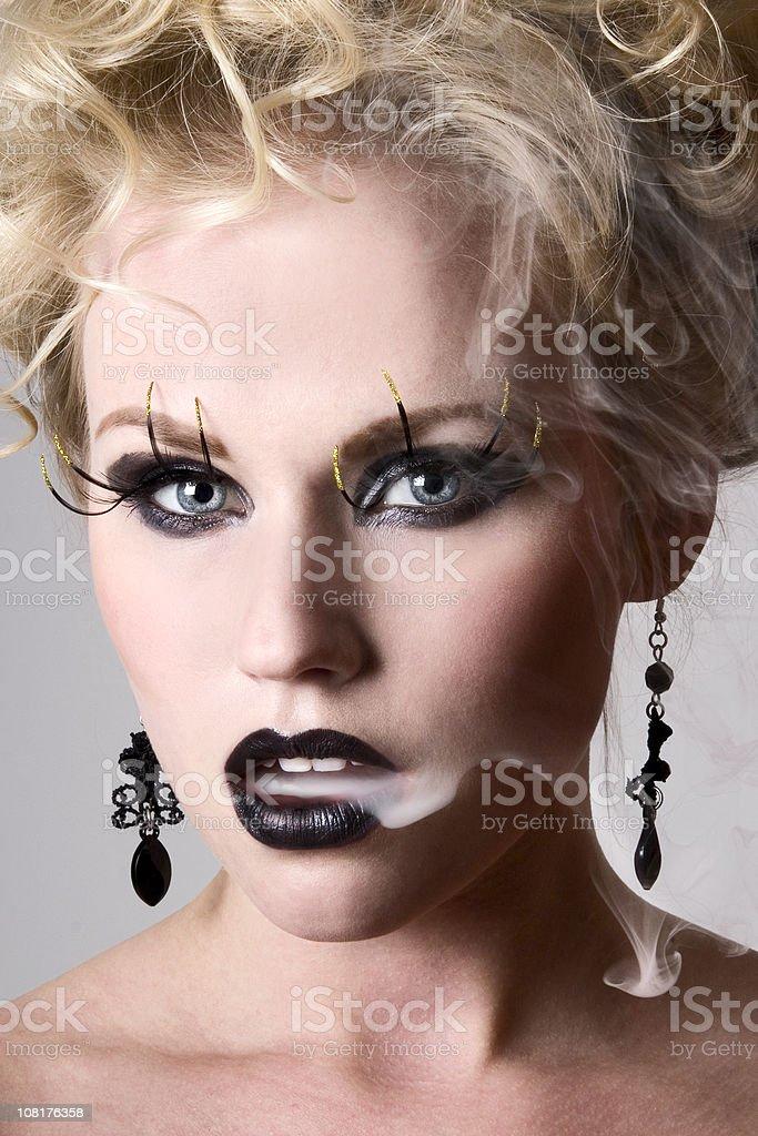 Woman Wearing Black Lipstick and Blowing Smoke From Mouth stock photo