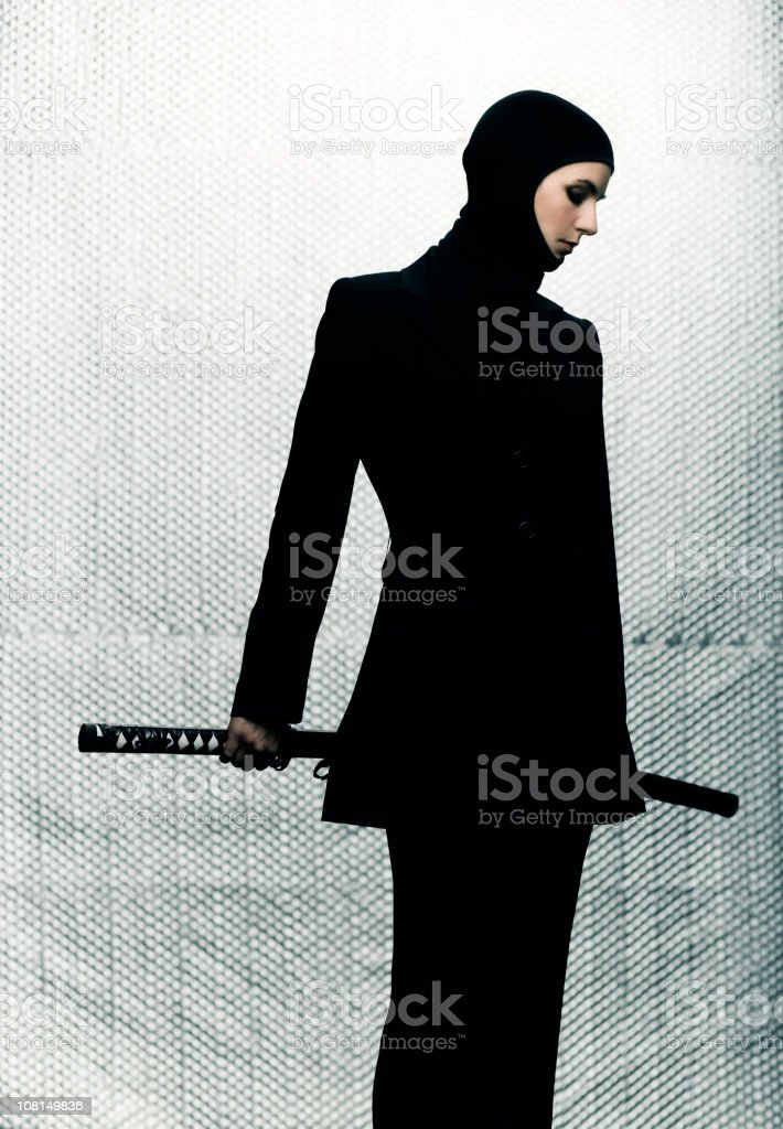 Woman Wearing Black Suit with Hood and Holding Ninja Sword stock photo