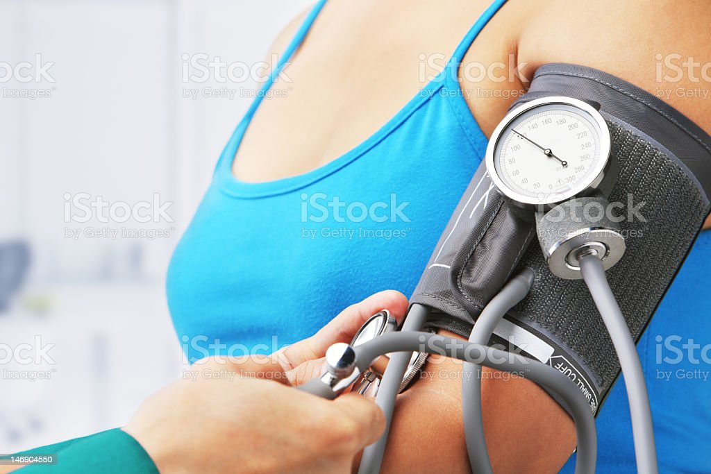 Woman wearing blue tank top getting blood pressure checked stock photo