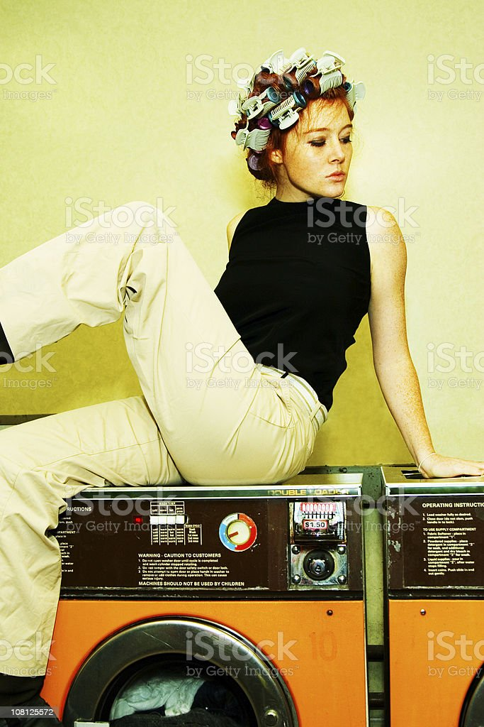 Woman Wearing Curlers Sitting on Top of Retro Washer royalty-free stock photo