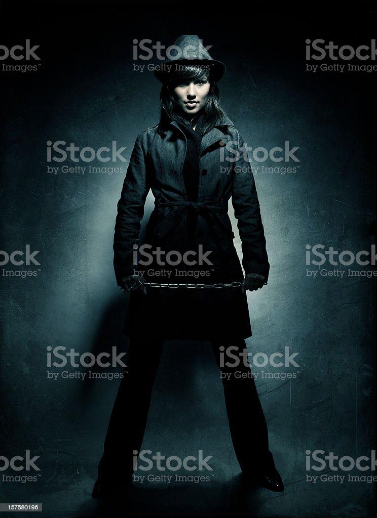 woman wearing dark coat holding a chain stock photo