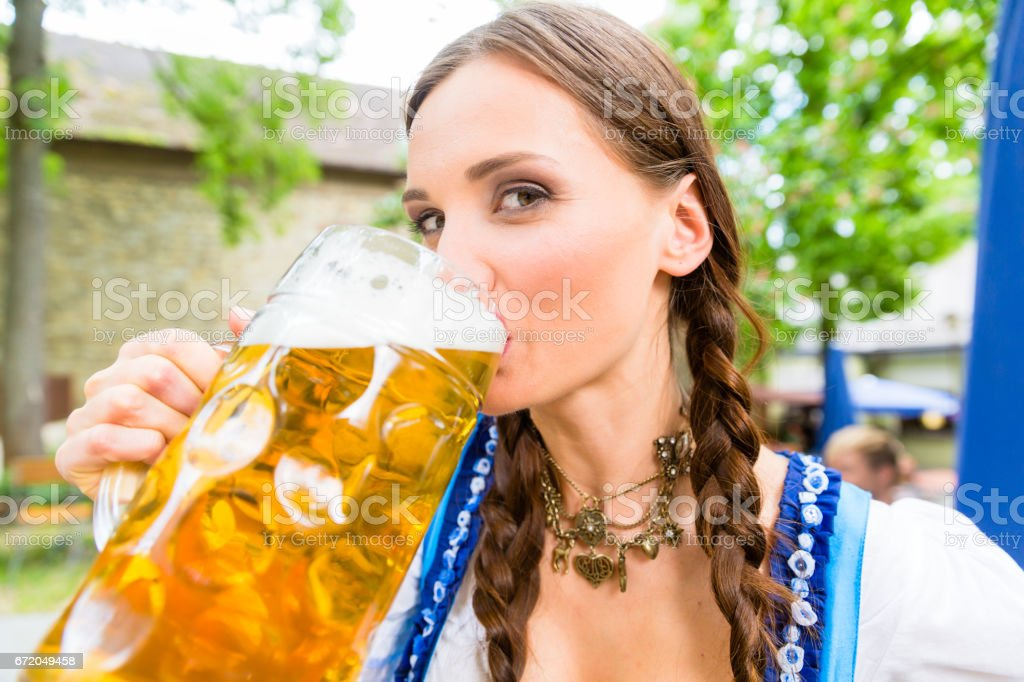 Woman wearing Dirndl drinking beer stock photo