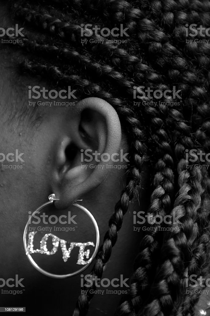 Woman Wearing Earring That Spells 'Love', Black and White royalty-free stock photo
