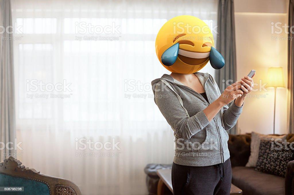 Woman wearing emoji masks while looking at her phone. stock photo