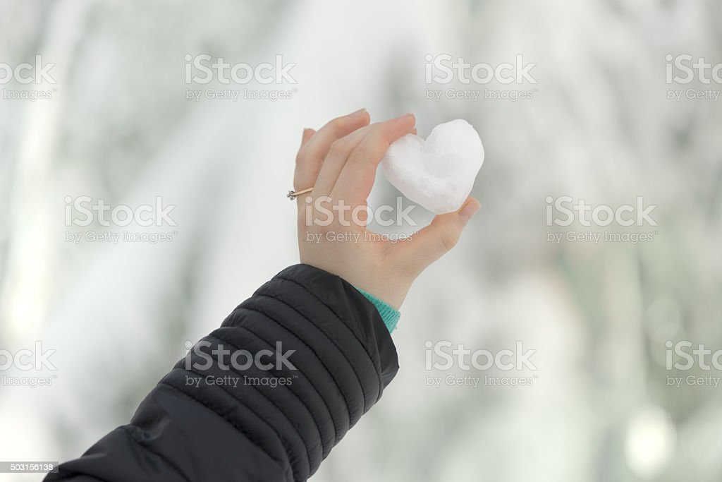 Woman Wearing Engagement Ring Holding Heart Made From Snow stock photo