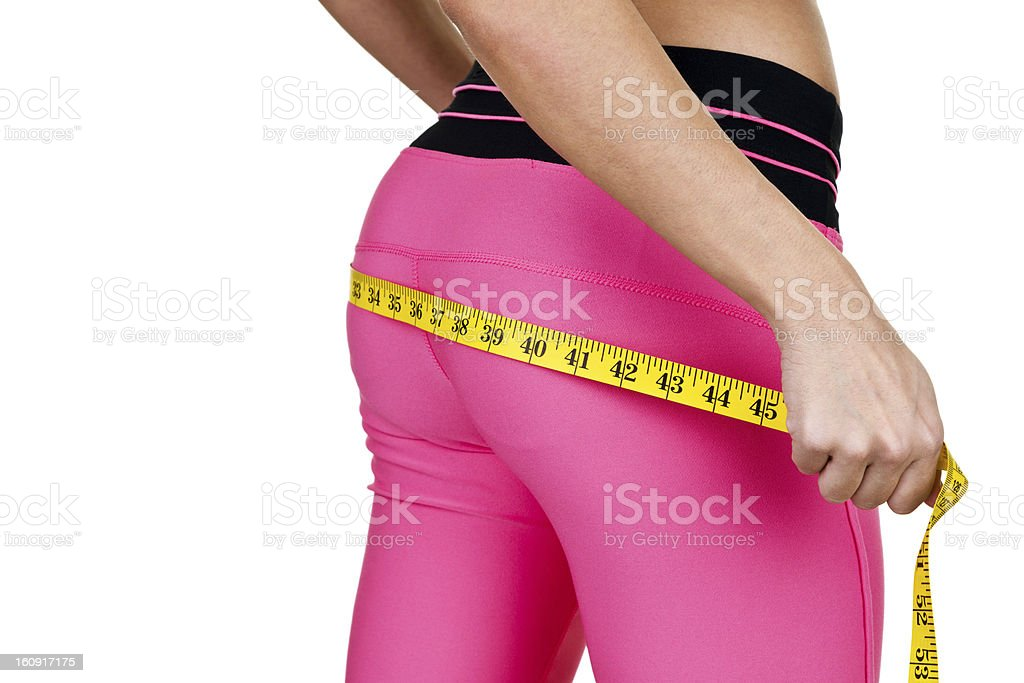 Woman wearing fitness clothing measuring her buttocks stock photo
