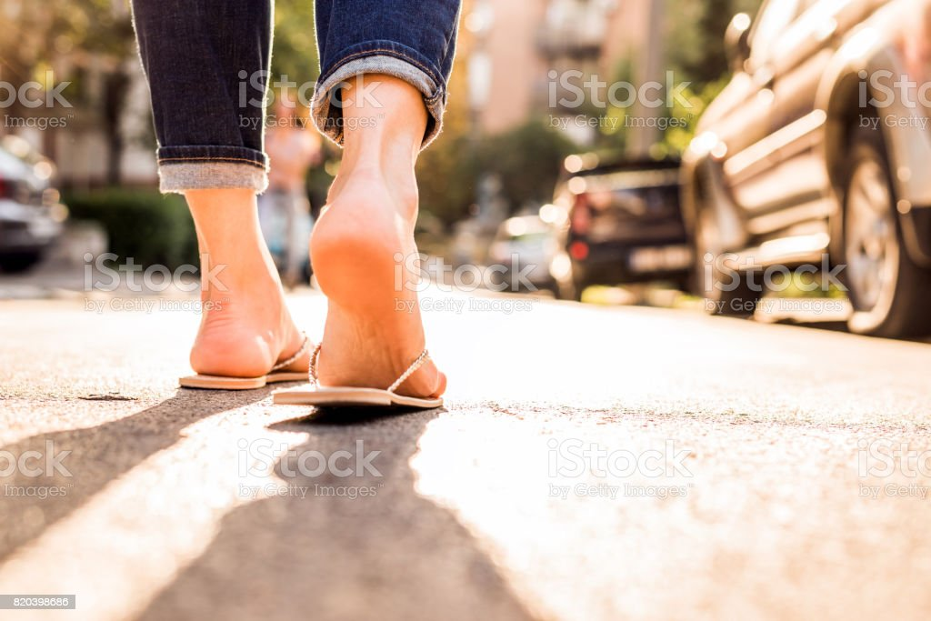 Woman wearing FlipFlops walking down the street on a sunny summer day- closeup of the feet stock photo