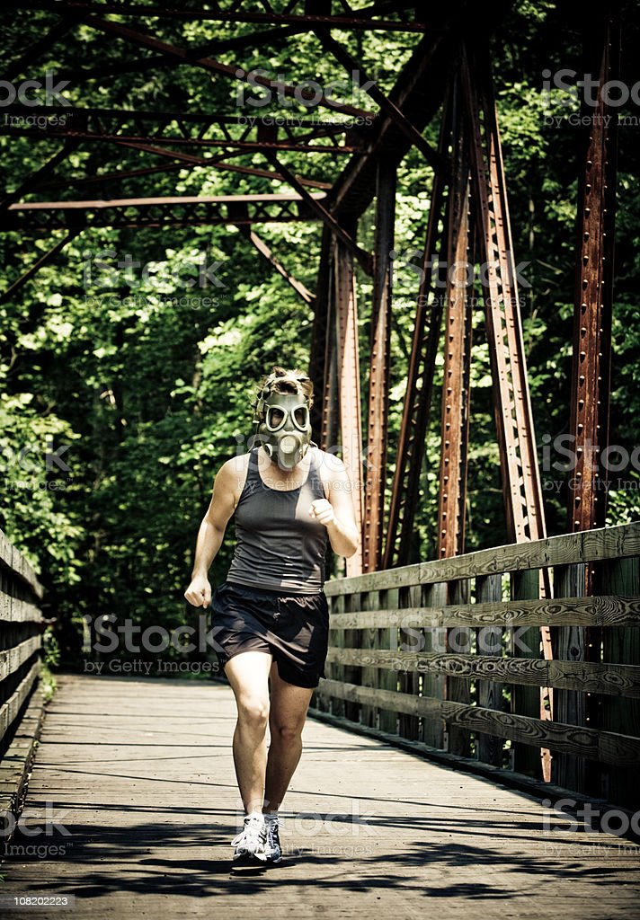 Woman Wearing Gas Mask While Running stock photo