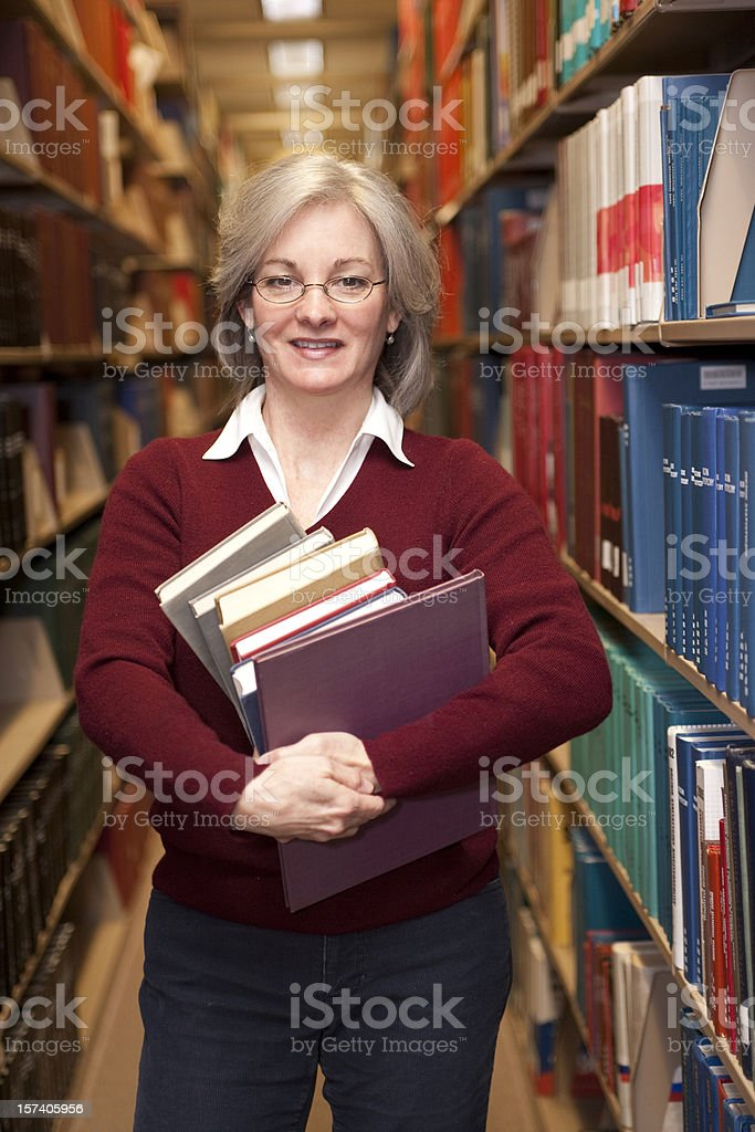 Woman wearing glasses carrying books (Library Series AXLE) royalty-free stock photo