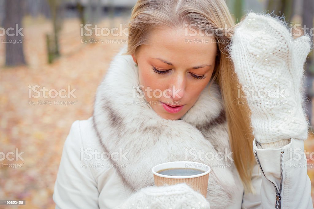 Woman wearing gloves and drinking coffee stock photo