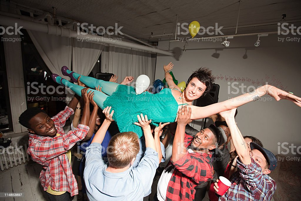 Woman wearing green dress at party crow surfing stock photo