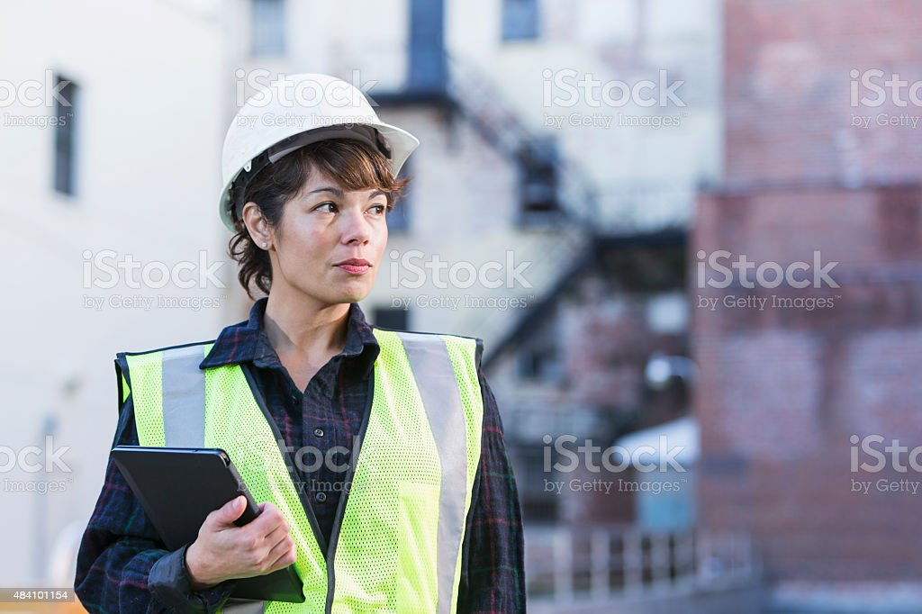 Woman wearing hard hat holding digital tablet stock photo