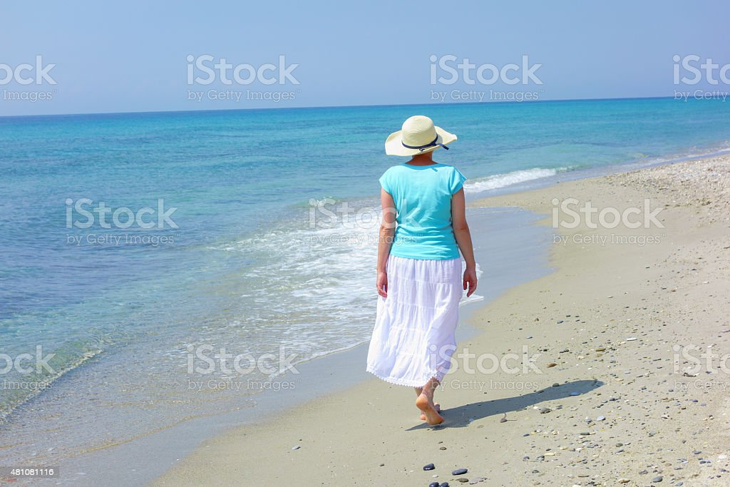 Woman wearing hat looking at sea stock photo