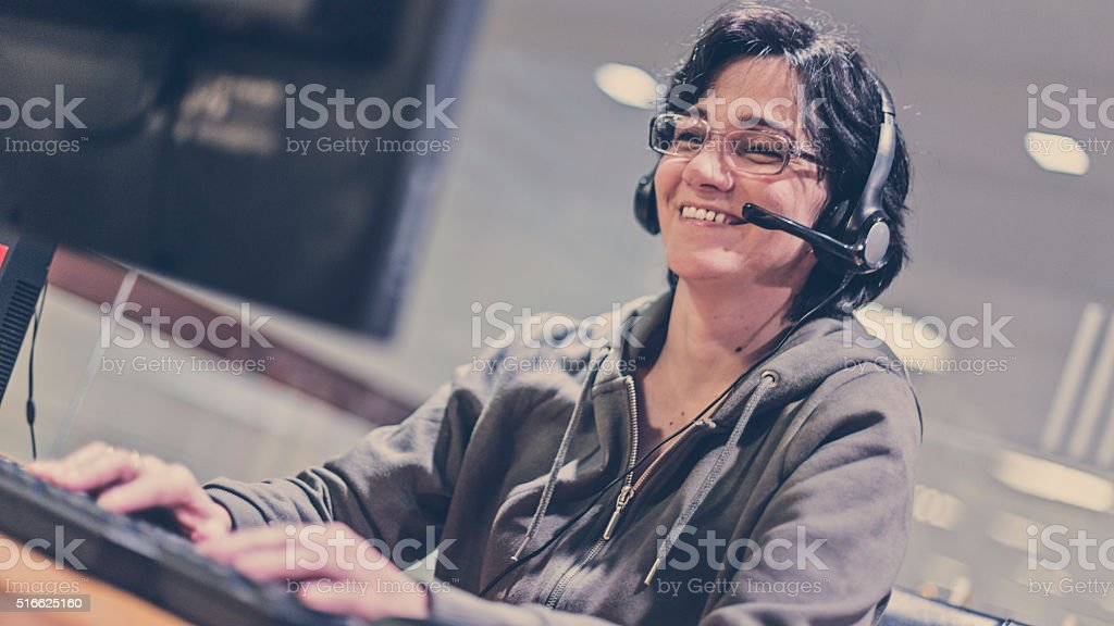 Woman wearing headset in computer room stock photo