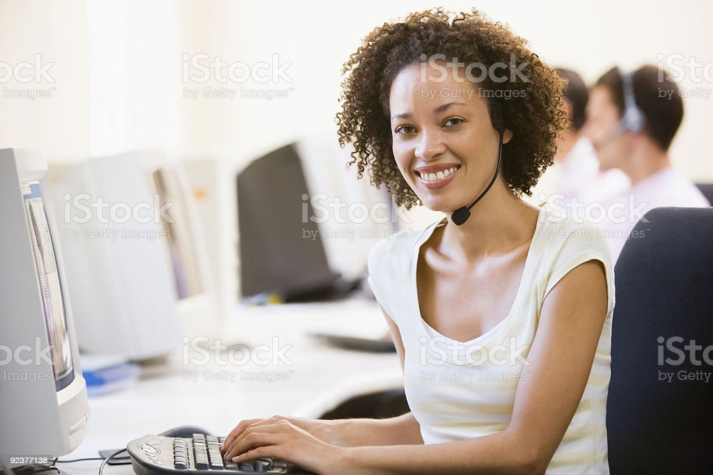Woman wearing headset in computer room royalty-free stock photo