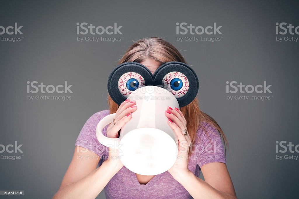 Woman Wearing Humorous Eyeball Glasses While Chugging Coffee stock photo