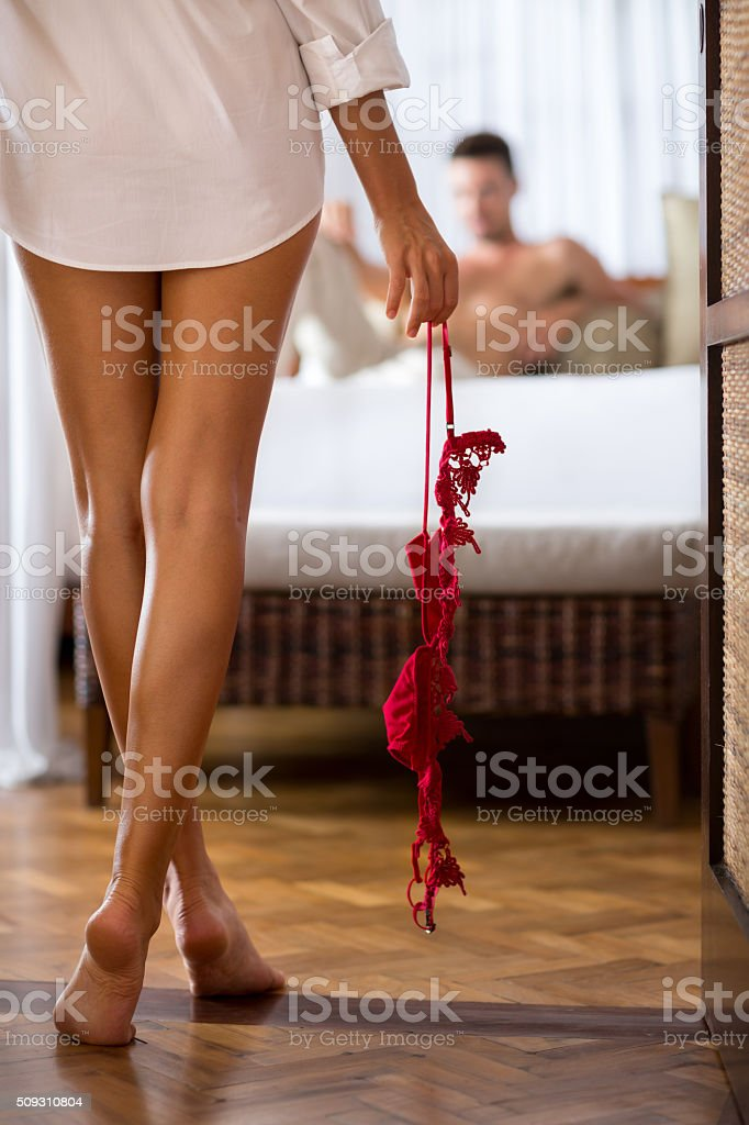 woman wearing  in only a shirt seductive enters the bedroom stock photo