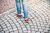 Woman wearing jeans and leather shoes walking on cobblestone