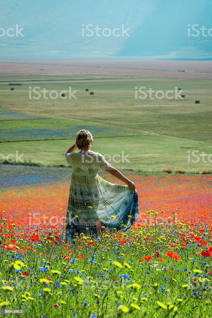Woman wearing long Green-Blue Dress near Castelluccio, Italy stock photo