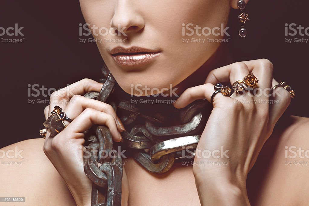 woman wearing luxury jewellery and heavy iron chain stock photo