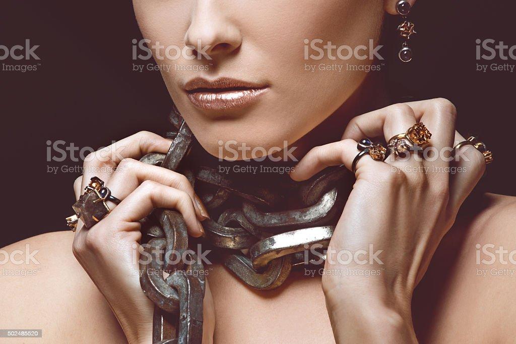 woman wearing luxury jewellery and heavy iron chain stock photo
