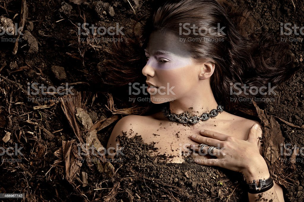woman wearing luxury jewellery laying down in dirt stock photo