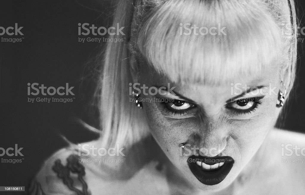 Woman Wearing Make-up and Facial Piercings Making Face stock photo