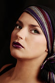 Woman Wearing Make-Up and Head Scarf on Black Background