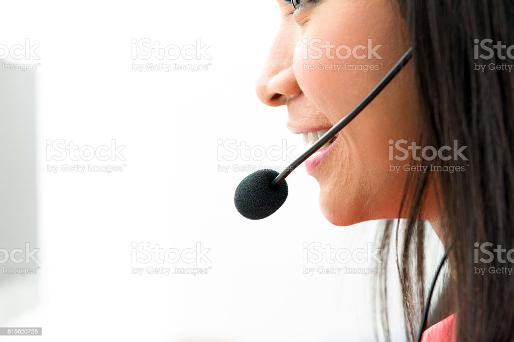 Woman wearing microphone headset in call center stock photo
