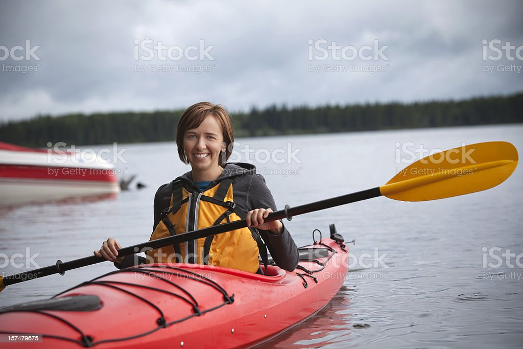 A woman wearing orange on a river in a red kayak royalty-free stock photo