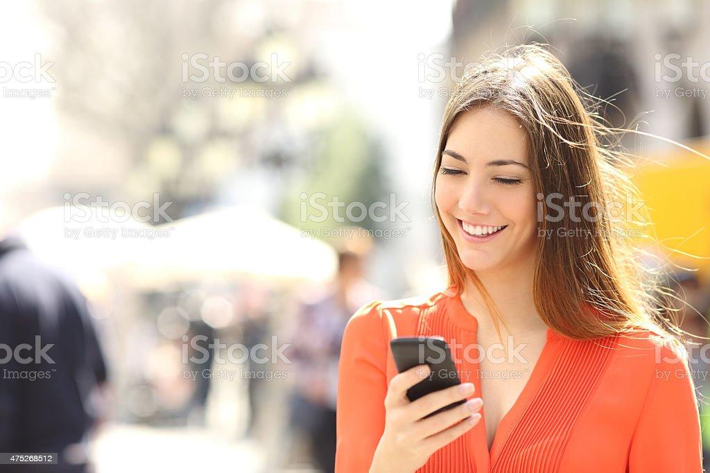 Woman wearing orange shirt texting on the smart phone stock photo
